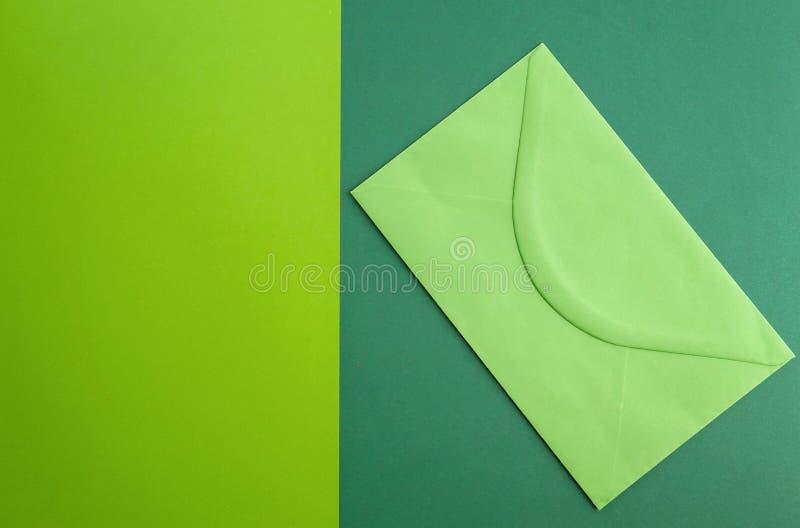 Grönt kuvert på färgglad grönskabakgrund Minsta begrepp royaltyfri bild