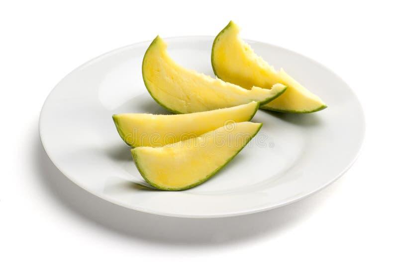 Grönt mangosnitt in i stycken i en platta som isoleras på vit bakgrund royaltyfri foto