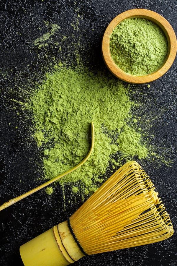 Grönt matchatepulver med bambu viftar, skedar och bowlar royaltyfria foton