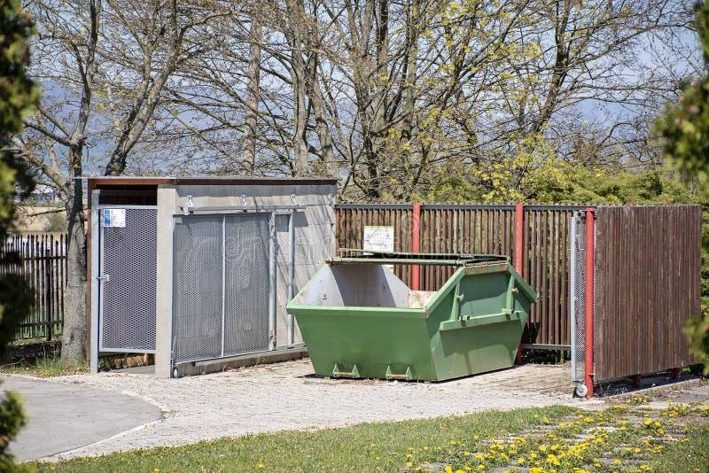 Grönt metallöverhopp Industriellt racka ner på överhoppet framme av trästaketet Racka ner på stället Tom dumpster royaltyfri foto