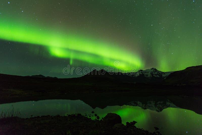 Grönt morgonrodnadljus bak sjöberget i sydliga Island Europa på nationalparkskaftafell royaltyfria bilder