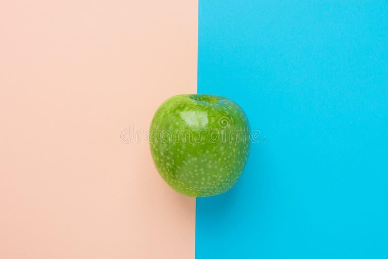 Grönt organiskt äpple på bakgrund för peachy rosa mintkaramell för duotone blå Sunda vitaminer bantar sommarDetoxstrikt vegetaria arkivfoto