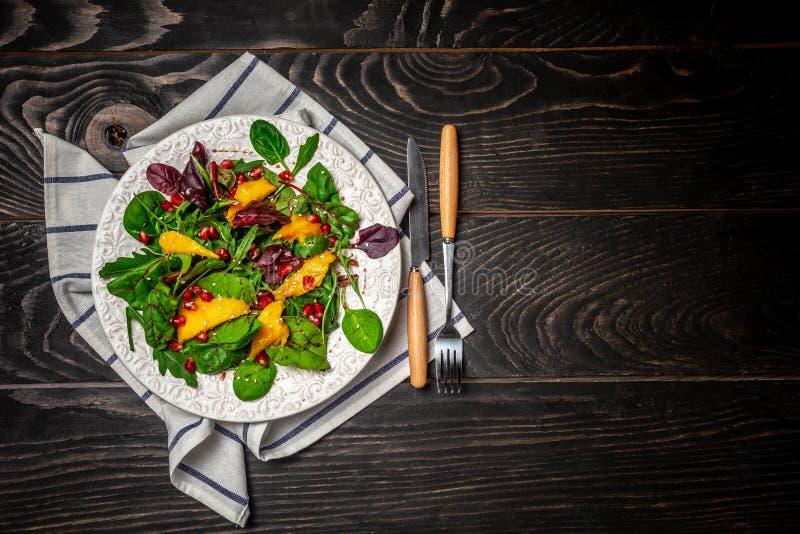 Grönt strikt vegetarianfrukostmål i bunkewithfarugula, mango och granatäpplet, vitaminmellanmål på en svart träbakgrund Begrepp a arkivfoto