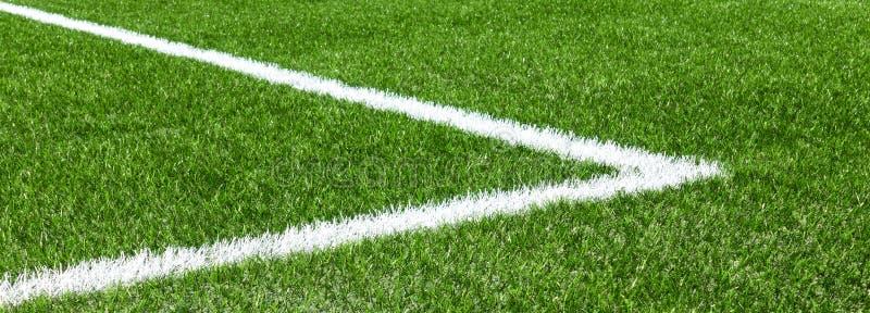 Grönt syntetiskt konstgjort fält för gräsfotbollsportar med den vita hörnbandlinjen arkivbilder