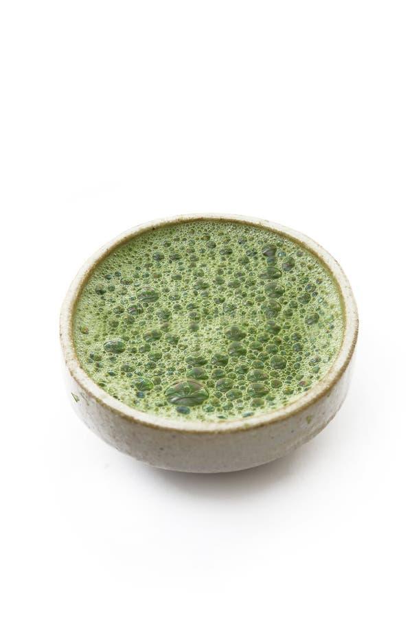 Grönt te för varm matcha i en kopp på en vit bakgrund royaltyfria foton