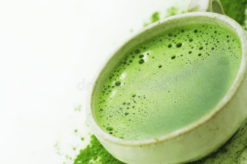 Grönt te för varm matcha i en kopp på en vit bakgrund royaltyfri fotografi