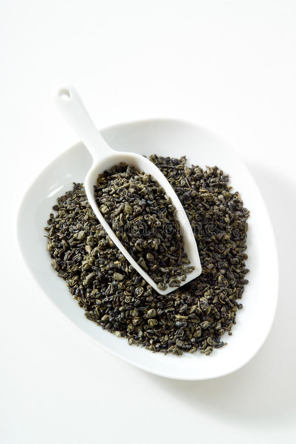 Grönt te, gunpowder te, bunke, vit bakgrund royaltyfri bild