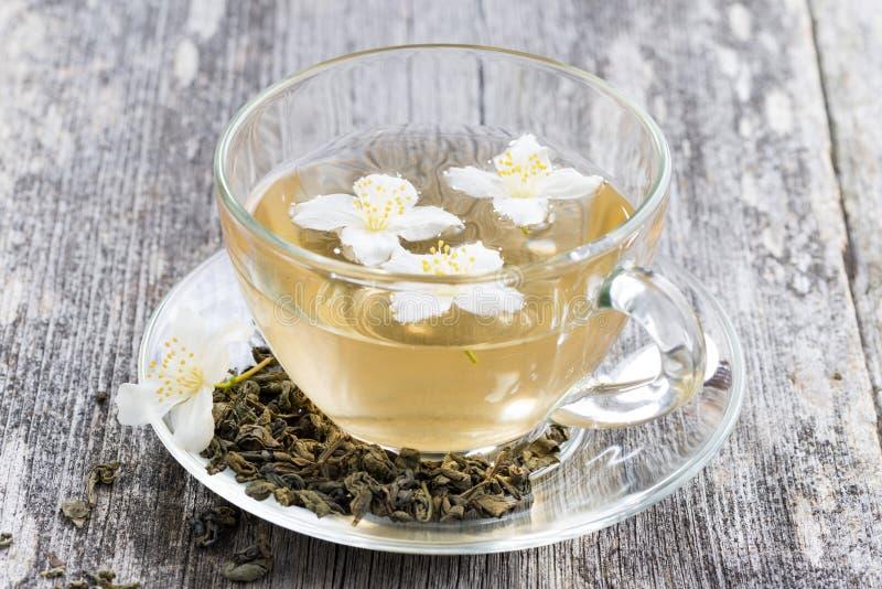 Grönt te med jasmin på trätabellen arkivbilder