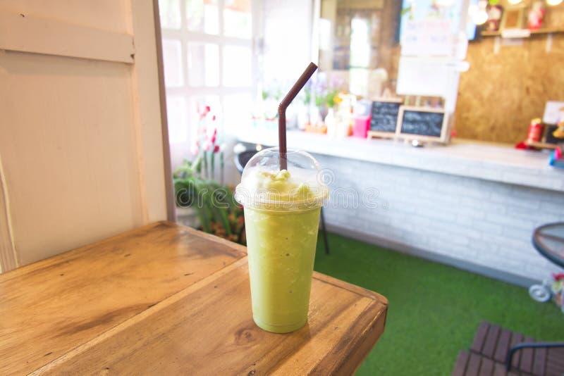 Grönt te mjölkar frappe i klart plast- exponeringsglas har brunt sugrör på den wood hyllan arkivfoton