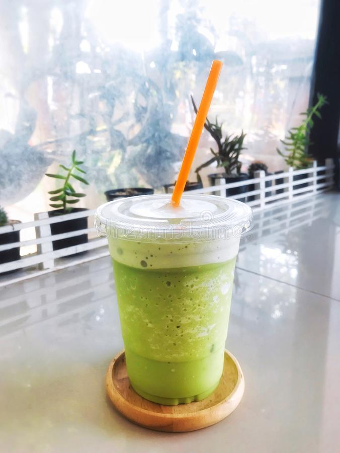 Grönt te mjölkar frappe i klart plast- exponeringsglas har orange sugrör i pålagd äta middag tabell för trämagasin med kaktuns, s arkivfoton