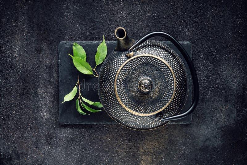 Grönt teblad med den svarta tekannan royaltyfria bilder