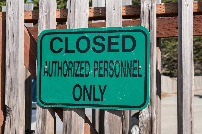 Grönt tecken som läser stängda behöriga personaler som postas endast på ett staket royaltyfri foto