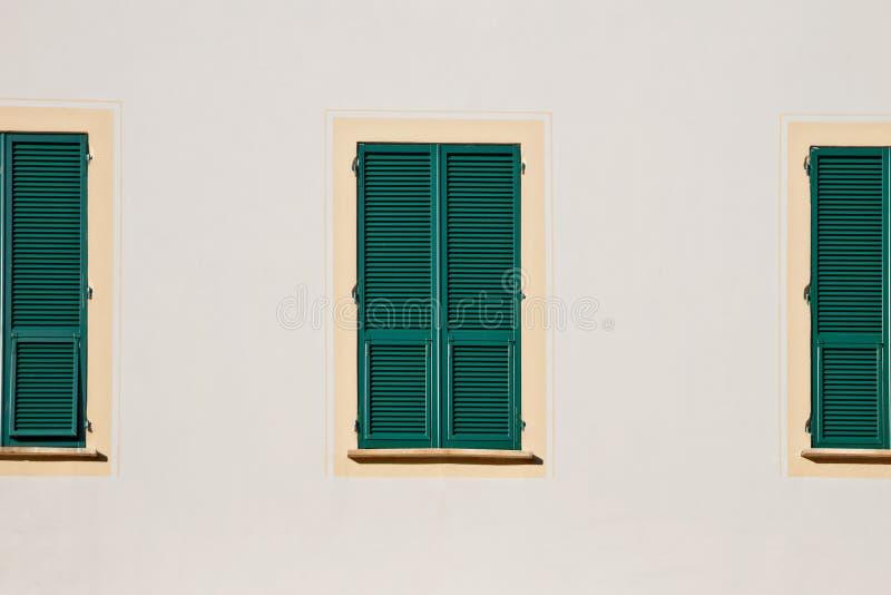 Grönt träfönster tre med slutare i gul ram på den vita väggen royaltyfri foto