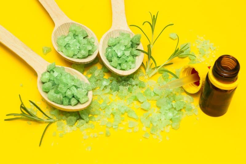 Grönt växt- saltar och oljer på en gul bakgrund arkivfoto