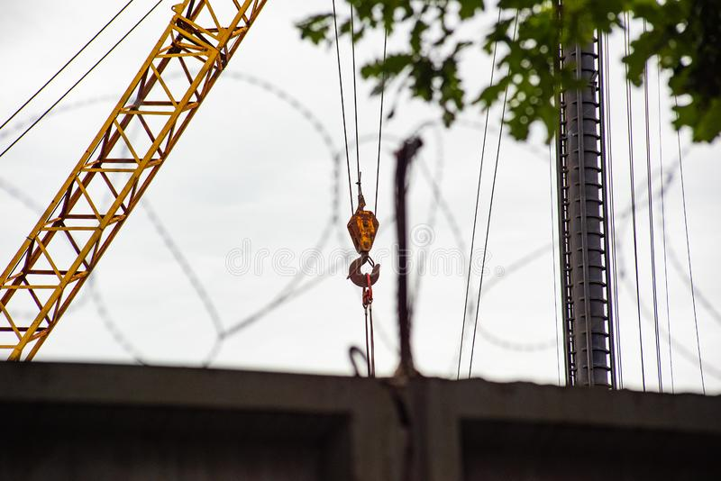 Grúa amarilla de la construcción detrás de una cerca del alambre de púas imagen de archivo libre de regalías
