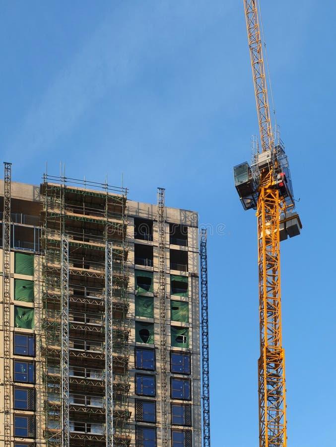 grúa amarillo alto que trabaja en un edificio concreto de la subida grande de la altura con el andamio contra un cielo azul foto de archivo libre de regalías