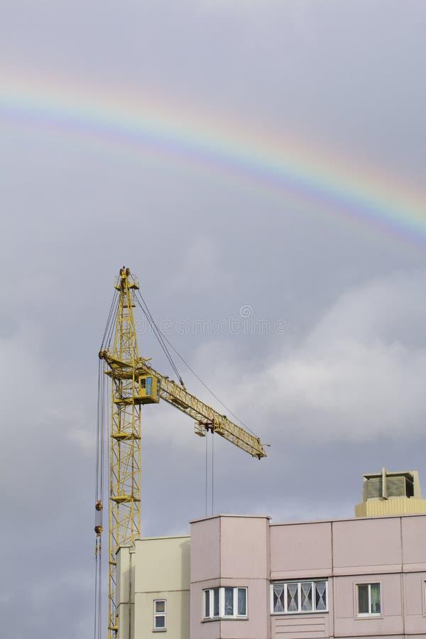 Grúa amarillo contra el cielo azul Sobre él está un arco iris después de una lluvia fotografía de archivo