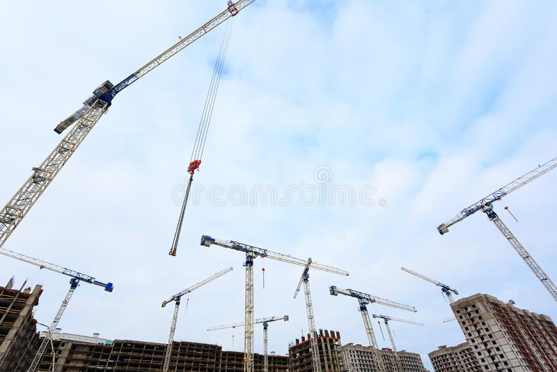 Grúa contra el cielo azul con los tejados de edificios de varios pisos bajo construcción de debajo fotos de archivo libres de regalías