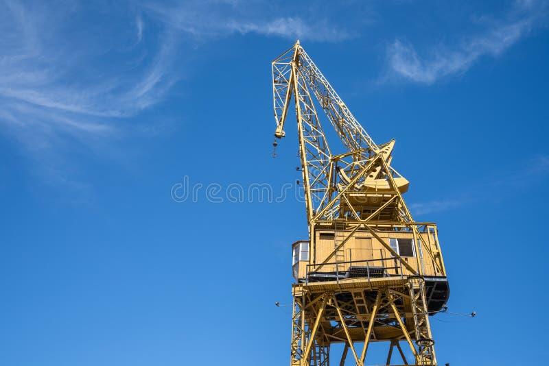 Grúa de construcción amarilla alta con el cielo azul, la herramienta o la máquina clara a la elevación enorme y pesada para el de fotografía de archivo