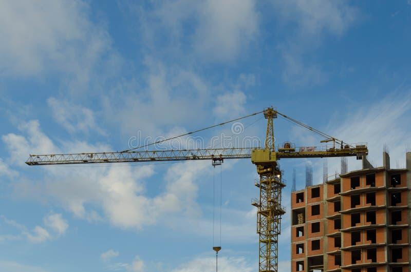 Grúa de construcción amarilla en el emplazamiento de la obra de una casa residencial del ladrillo en un fondo del cielo azul con  imagen de archivo