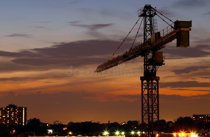 Grúa de construcción en la noche imagenes de archivo