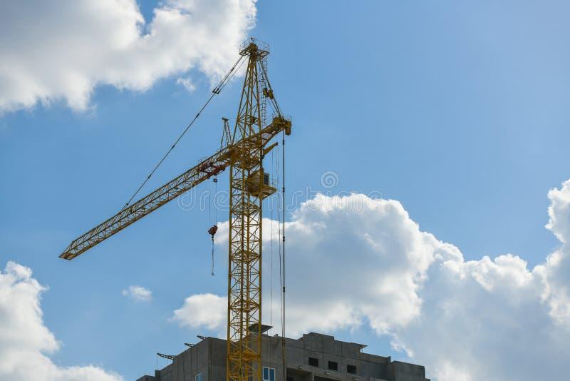 Grúa de construcción de gran altura con una flecha larga del color amarillo contra el cielo azul sobre un nuevo edificio de vario fotos de archivo libres de regalías