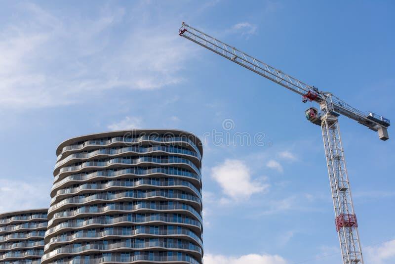 Grúa de construcción grande con el apartamento moderno de gran altura dos imagenes de archivo