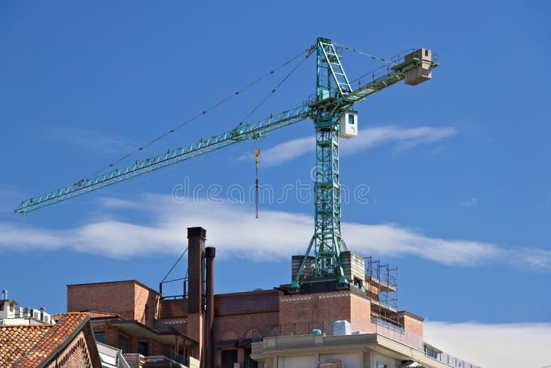 Grúa de construcción montada en el tejado de un edificio en Milán fotografía de archivo