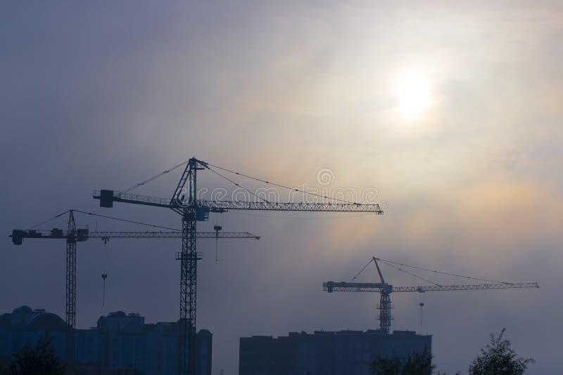 grúa de construcción muy alta en la niebla de la mañana, contra el fondo gris del cielo imagen de archivo libre de regalías