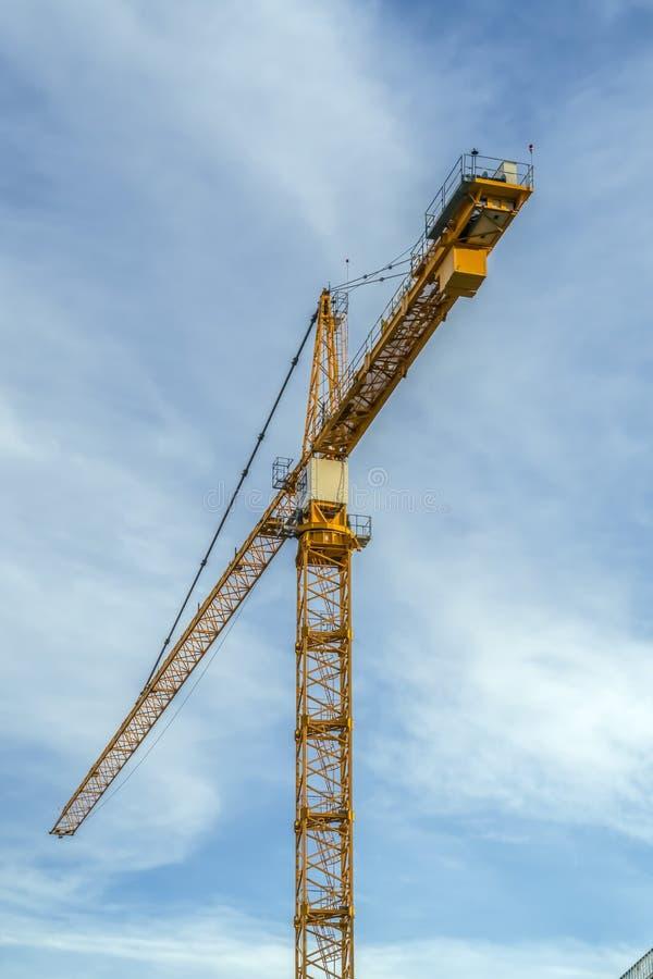 Grúa de la construcción contra el cielo azul nublado fotografía de archivo