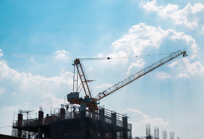 Grúa de trabajo en el edificio del tejado con el cielo azul y la nube imagenes de archivo