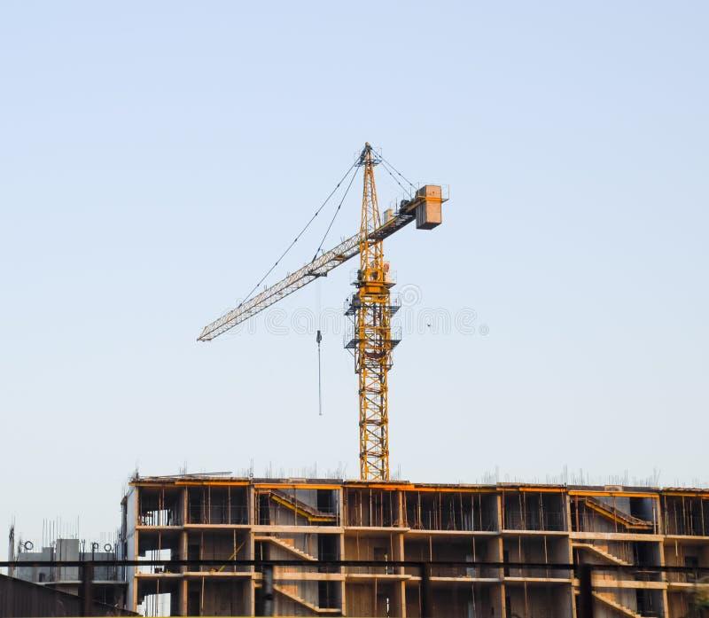 Grúa del edificio de la torre cerca de la nueva casa bajo construcción fotografía de archivo libre de regalías