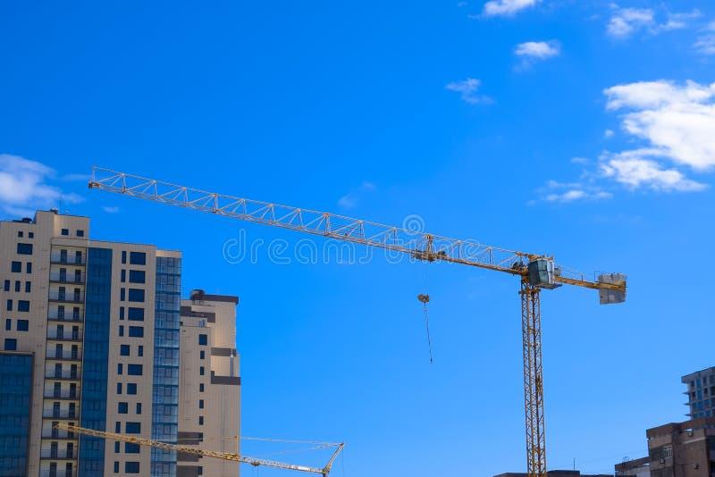 Grúa del edificio de la torre contra el cielo azul y el sol Construcción de nuevos edificios con una grúa Grúa rojo imágenes de archivo libres de regalías