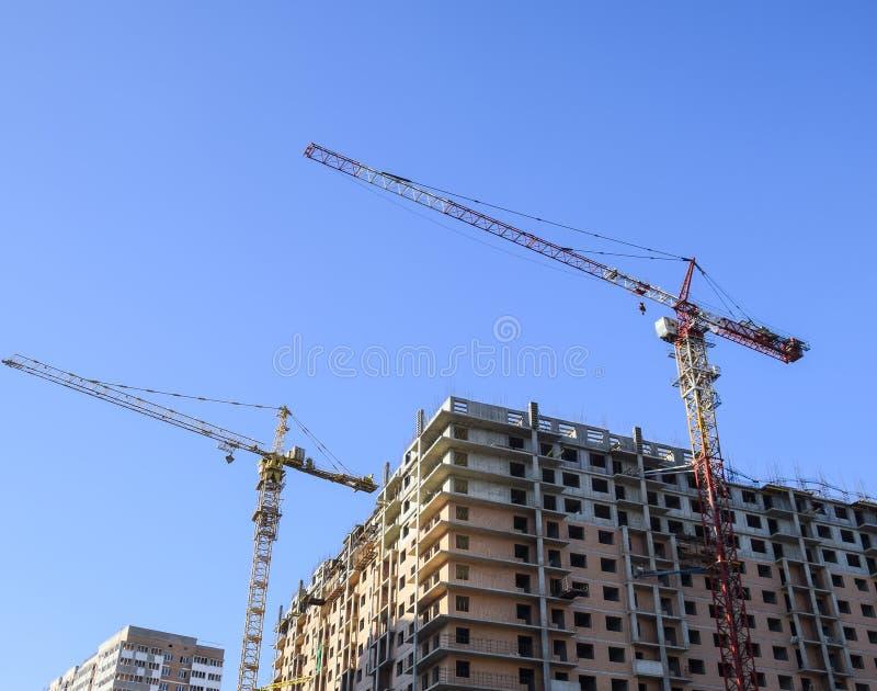 Grúa del edificio de la torre contra el cielo azul y el sol Construcción de una nueva casa Construcción de nuevos edificios con u fotografía de archivo libre de regalías