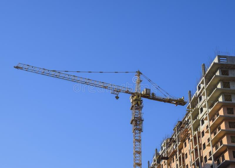 Grúa del edificio de la torre contra el cielo azul y el sol Construcción de una nueva casa Construcción de nuevos edificios con u foto de archivo