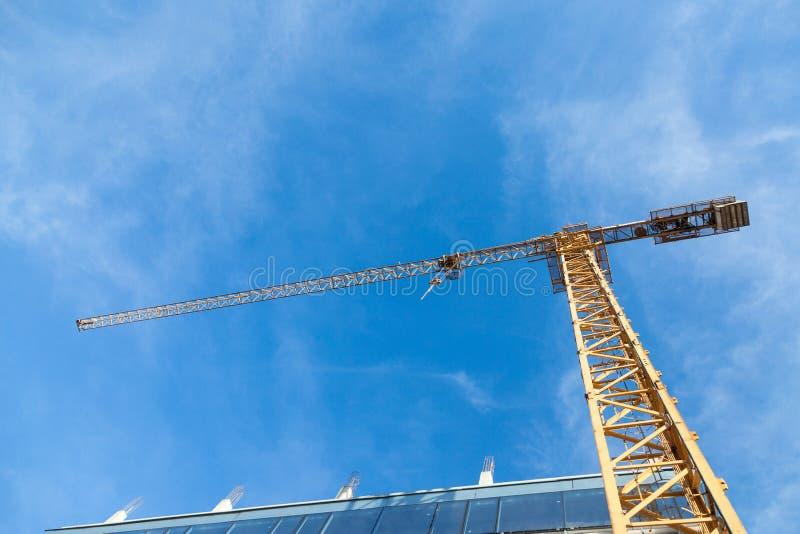 Grúa del metal amarillo delante de un edificio que es montado en un emplazamiento de la obra tomado de debajo durante una tarde s fotos de archivo libres de regalías