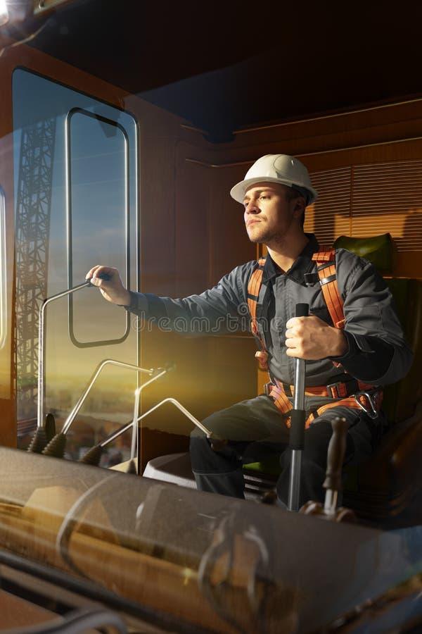 Grúa del operador del ingeniero en la acción Él sienta un top en cabina y el trabajo de la grúa imagen de archivo libre de regalías