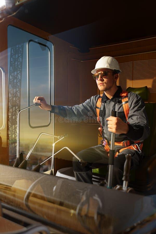 Grúa del operador del ingeniero en la acción Él sienta un top en cabina y el trabajo de la grúa imágenes de archivo libres de regalías