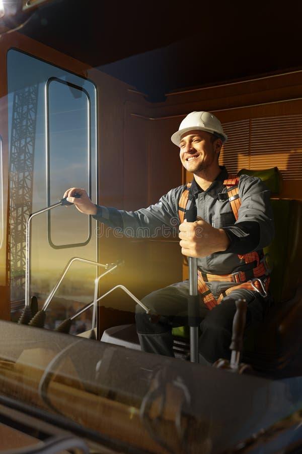 Grúa del operador del ingeniero en la acción Él sienta un top en cabina y el trabajo de la grúa fotografía de archivo libre de regalías