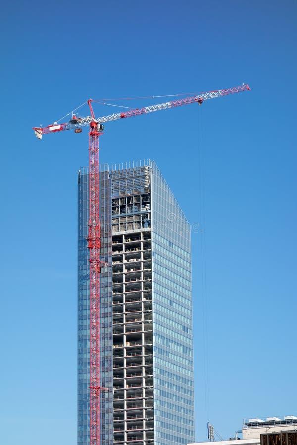 Grúa encima del rascacielos de la construcción que construye sobre el cielo azul imágenes de archivo libres de regalías