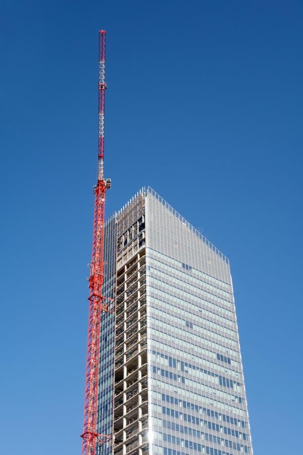 Grúa encima del rascacielos de la construcción que construye sobre el cielo azul imagen de archivo