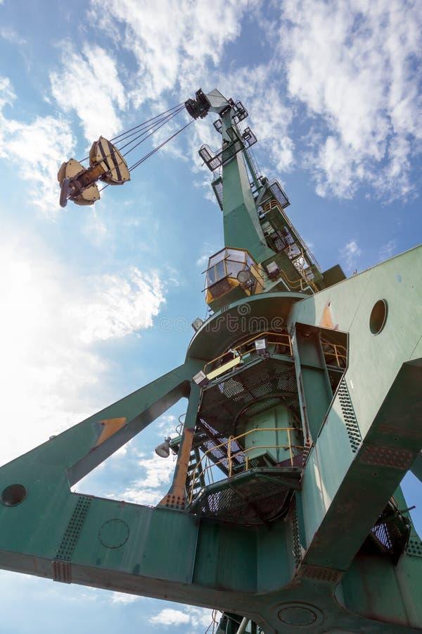Grúa industrial grande del puerto delante del cielo azul con las nubes blancas foto de archivo