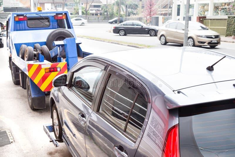 Grúa que remolca un coche analizado en la calle imagen de archivo