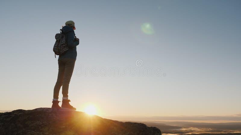 Grúa tirada: Un viajero de la mujer se coloca encima de una montaña, mira el paisaje hermoso a continuación, admira la naturaleza fotografía de archivo