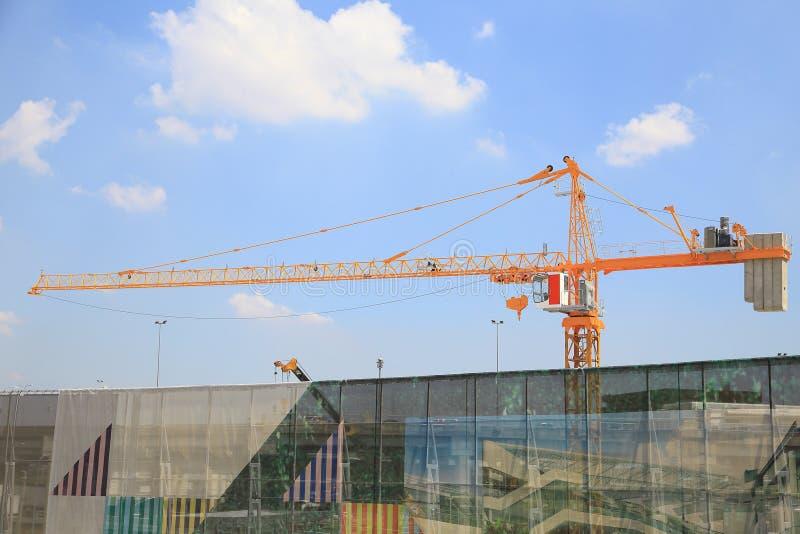 Grúas amarillas en emplazamiento de la obra con el cielo azul y la nube, como fondo de la arquitectura imagen de archivo libre de regalías