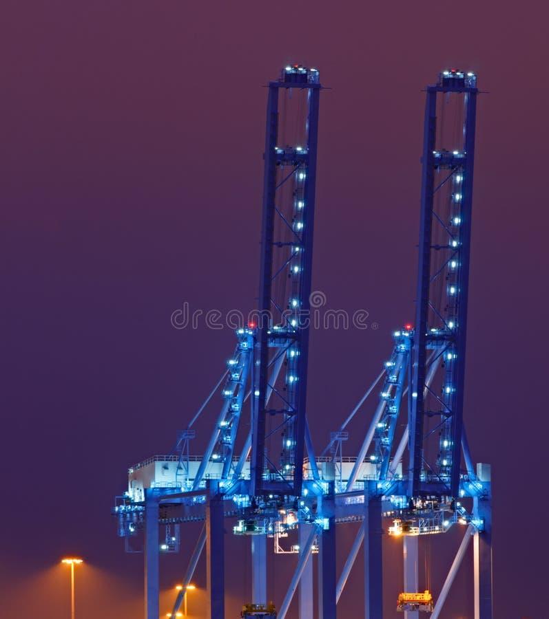 Grúas azules del muelle en la noche fotos de archivo