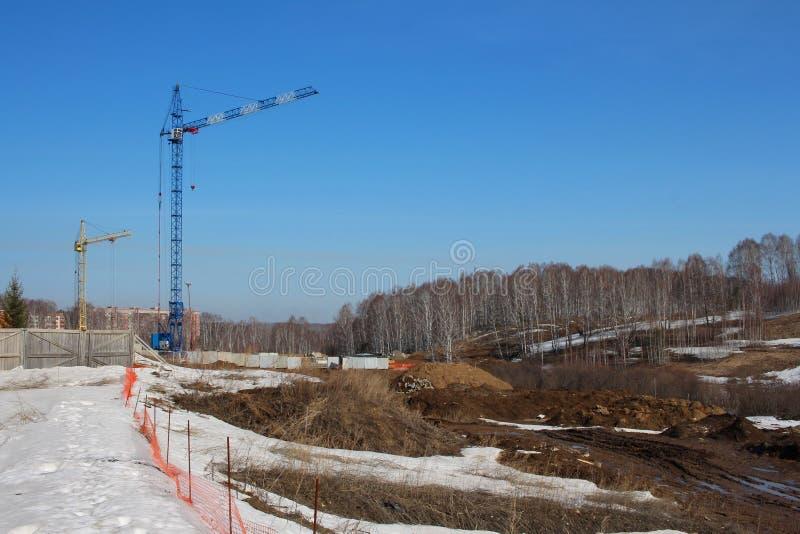 Grúas de construcción que construyen el nuevo desarrollo de los edificios de la tierra tecnologías de la industria de la urbaniza imagenes de archivo