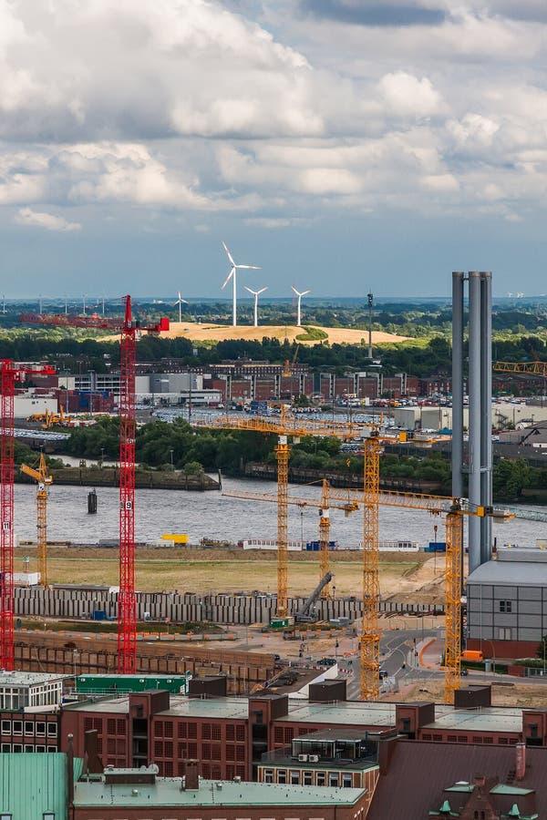 Grúas de construcción y turbinas de viento en Hamburgo fotografía de archivo
