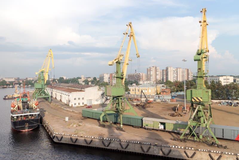 Grúas del puerto con el viejo warehose imagen de archivo