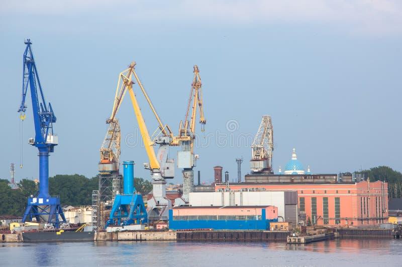 Grúas del puerto con el viejo warehose Puerto de StPetersburg fotos de archivo libres de regalías